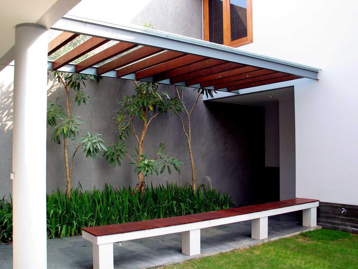Keindahan tropis di selasar dengan material kayu dan batu alam, serta tanaman irish dan tabebuia (Sumber: arsitag.com)