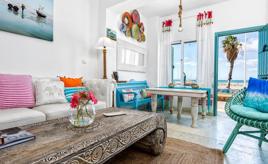 Kenyamanan suasana tropis yang segar tampil dari warna putih pada dinding dan sofa, serta warna turquoise yang unik dan menawan. Meja dengan ukiran bertema gelombang dan kursi rotan berulir menampilkan unsur etnik yang membuat ruang tamu kelihatan elegan. Sarung bantal sofa dalam berbagai ukuran dan warna bisa dibuat sendiri dari potongan kain. Hasil karya yang sederhana mampu membawa kenyamanan, sekaligus menjadi dekorasi yang membuat ruang tamu tampil stylish.