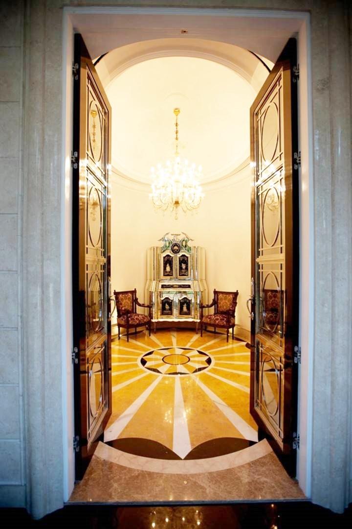 Ruang tamu dengan arsitektur klasik Eropa bisa menggunakan pintu kaca atau pintu mozaik. Seperti pada pintu masuk rumah Patiunus.