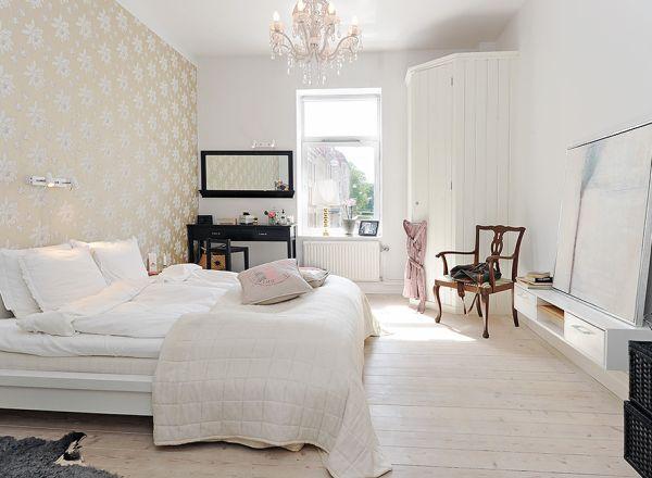 Anda bisa memasukkan unsur lain ke dalam kamar Skandinavian Anda untuk mendapatkan kesan yang lebih elegan. Desain di atas misalnya diberi tambahan chandelier berbahan kristal yang cantik dengan stiker dinding bercorak emas.