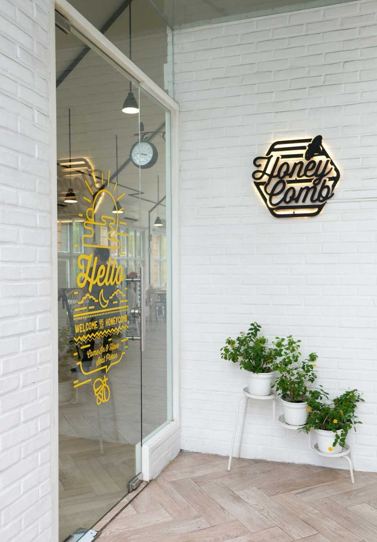 Di pintu masuk yang memperlihatkan dinding bata ekspos yang dicat putih, sebuah logo kecil berwarna hitam dengan lampu kuning di dinding akan menyambut Anda. Tiga buah pot berisi tanaman hijau menambah kesan asri dari café yang dibangun pada tahun 2015 ini; membuat siapapun semakin penasaran dengan suasana di dalamnya.