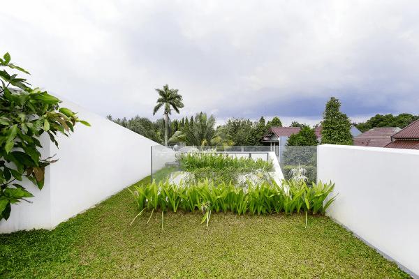 Taman minimalis yang ditumbuhi rerumputan dan white spider lily menjadi taman yang cukup nyaman untuk bersantai dan bermain, sekaligus mudah perawatannya. Kaca sebagai pengganti tembok taman, membuat taman terlihat semakin luas.