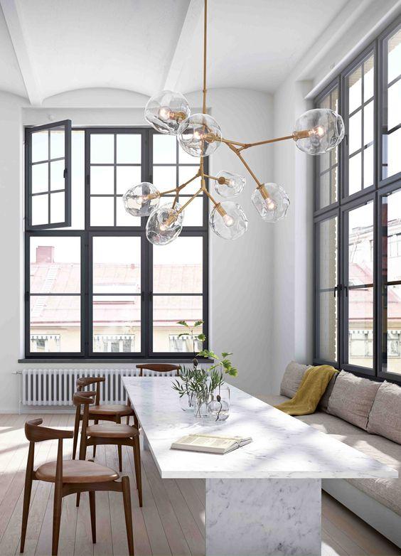 Lampu gantung dengan desain bola-bola kaca ini menonjolkan koleksi furnitur yang ditampilkan di ruang tamu ini.