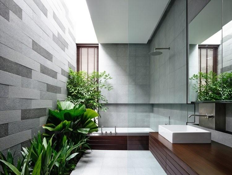 Sebagai ganti detail hiasan dan dekorasi, tambahkan tanaman hijau atau vas bunga di kamar mandi kontemporer sebagai kontras. Dalam contoh gambar ini, kamar mandi didominasi dengan material kayu dan beton ekspos. Warna kontras juga ditonjolkan pada closet dan wastafel warna putih.