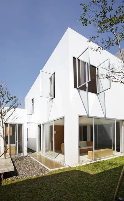 Ini adalah contoh model rumah minimalis yang umumnya dijumpai di Indonesia. Permainan geometris kotak dengan belahan jendela, garis awning, serta repetisi garis vertikal pada pagar menjadi ciri minimalis yang khas.
