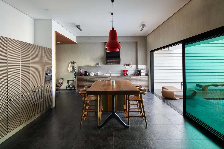 Meja kayu bersanding dengan dapur serba logam (Sumber: arsitag.com)