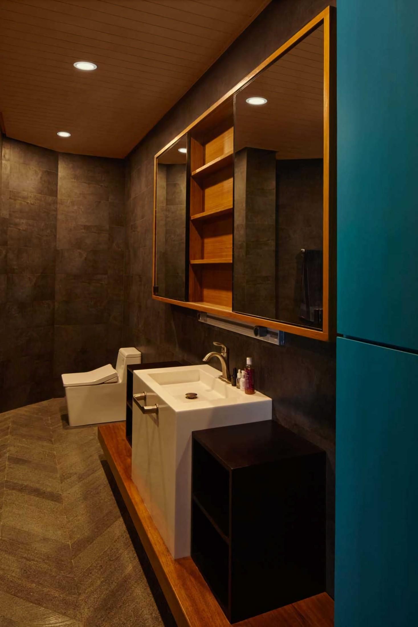 Tata pencahayaan downlightning pada plafon kayu model drop ceiling menerangi kamar mandi Na Residence, memantulkan warna gelap dari keramik dinding dengan lembut dan warna turquoise yang elegan.
