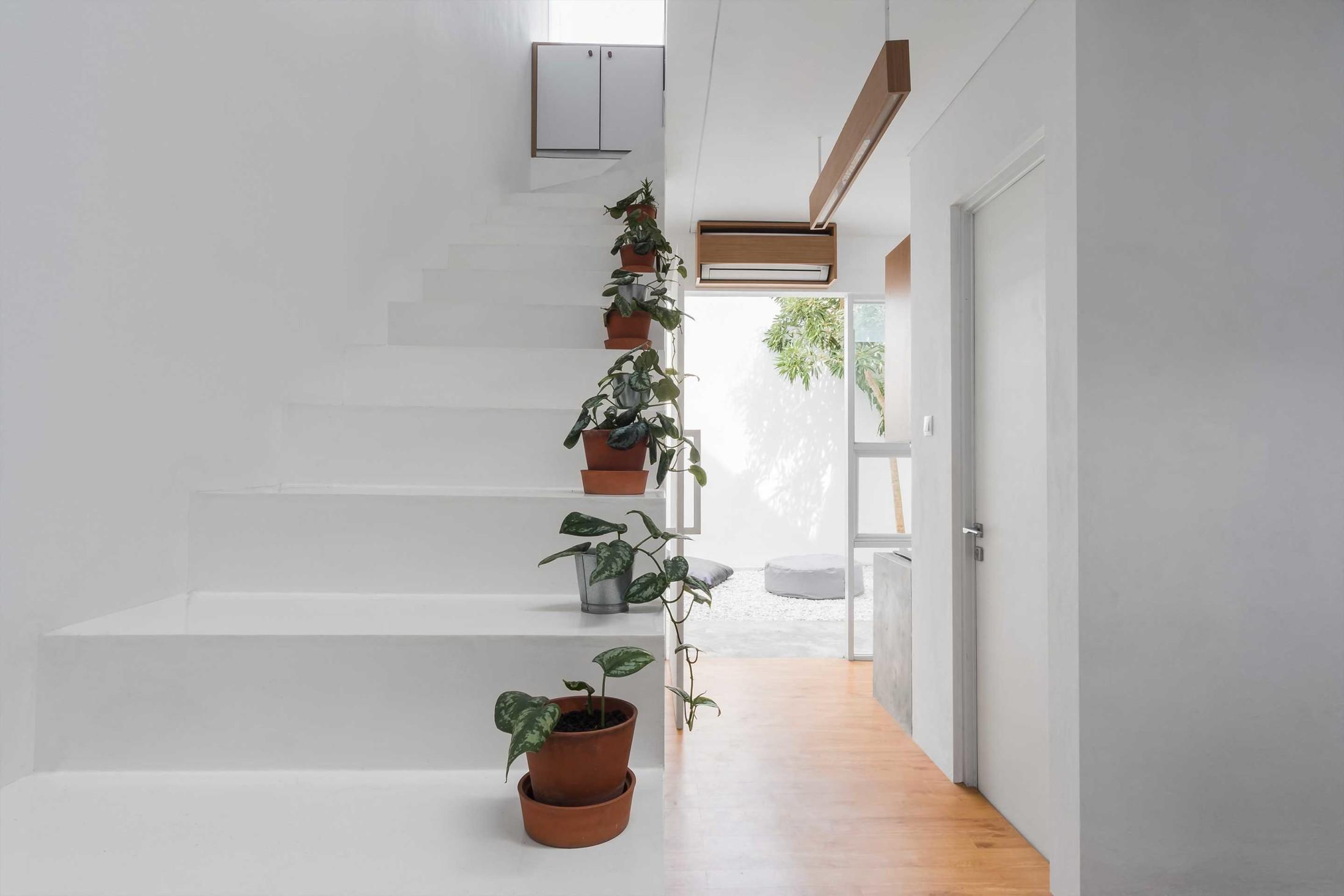 Tanaman dalam pot sebagai pembatas visual dan keamanan di pinggir tangga (Sumber: arsitag.com)