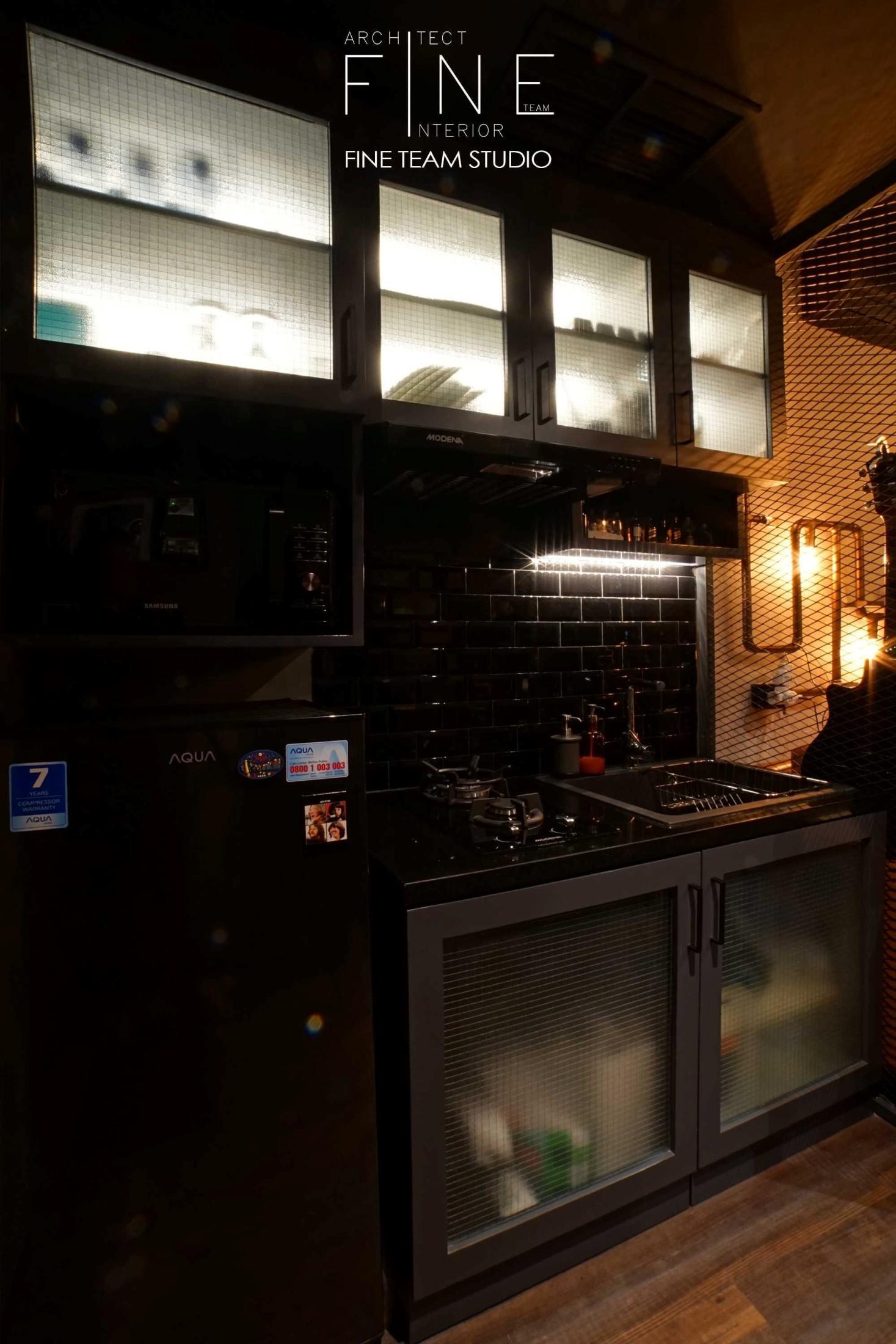 Konsistensi pemanfaatan material ditunjukkan dari pemakaian besi dicat hitam doff dan hitam glossy pada seluruh kitchen set hingga kulkas dan backsplash. Lampu downlight di bagian bawah lemari gantung menyoroti backsplash keramik, memantulkan kilau hitam yang memukau. Sticker kaca/sandblast motif jaring horizontal vertikal senada dengan partisi jaring besi motif diagonal pada perabotan lainnya. Lampu putih yang memancar lembut dari pintu kaca kabinet membuat kitchen set mungil tampil elegan.