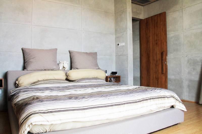 Desain interior kamar tidur cowok dengan permainan warna dan pola netral di Bare Minimalist karya RAW Architecture