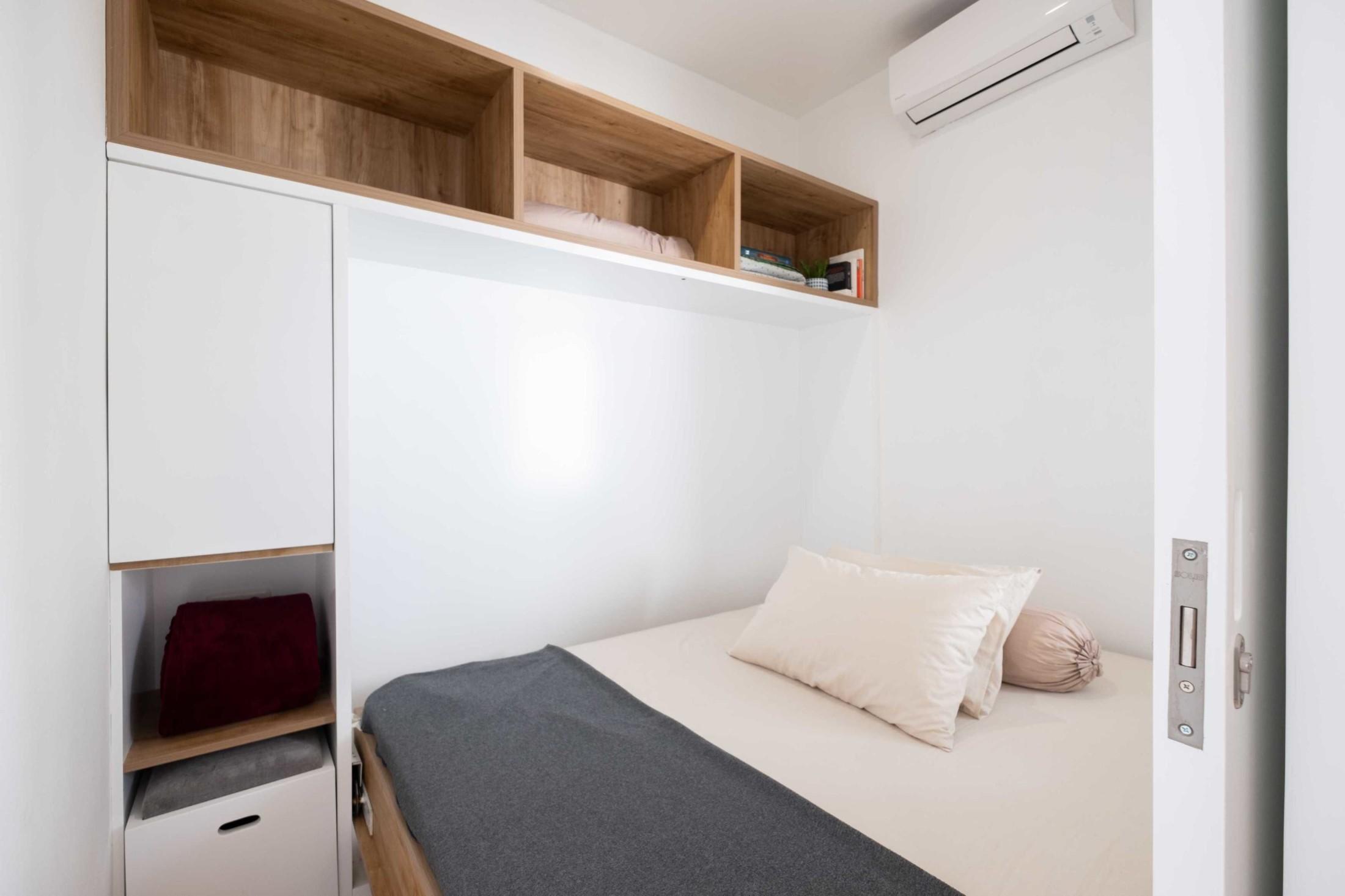 Saat tiba waktunya tidur, meja belajar itu berubah menjadi tempat tidur. Ternyata, ada sebuah murphy bed dengan engsel terkait pada rak dan dinding pengapitnya.