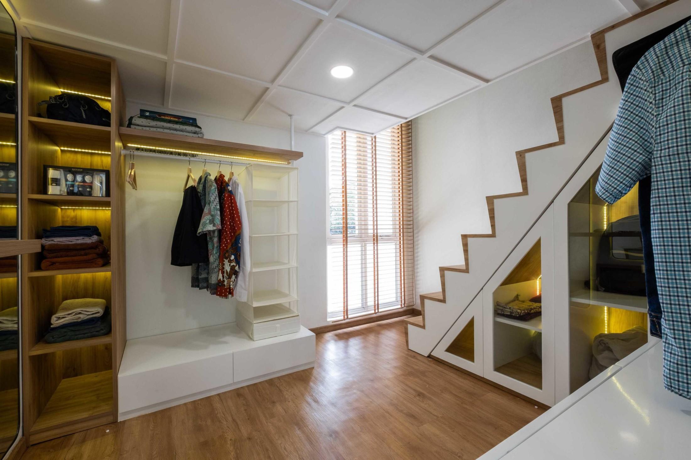Area walk-in closet yang berdampingan dengan tangga menunjukkan keunikan konsep desain interior rumah mungil ini dibanding rumah lainnya. Paduan warna putih glossy dengan warna alami dari kayu parket pada lantai, anak tangga, dan tirai menampilkan suasana yang hangat, natural, bersahaja, dengan tampilan yang bersih dan terang.
