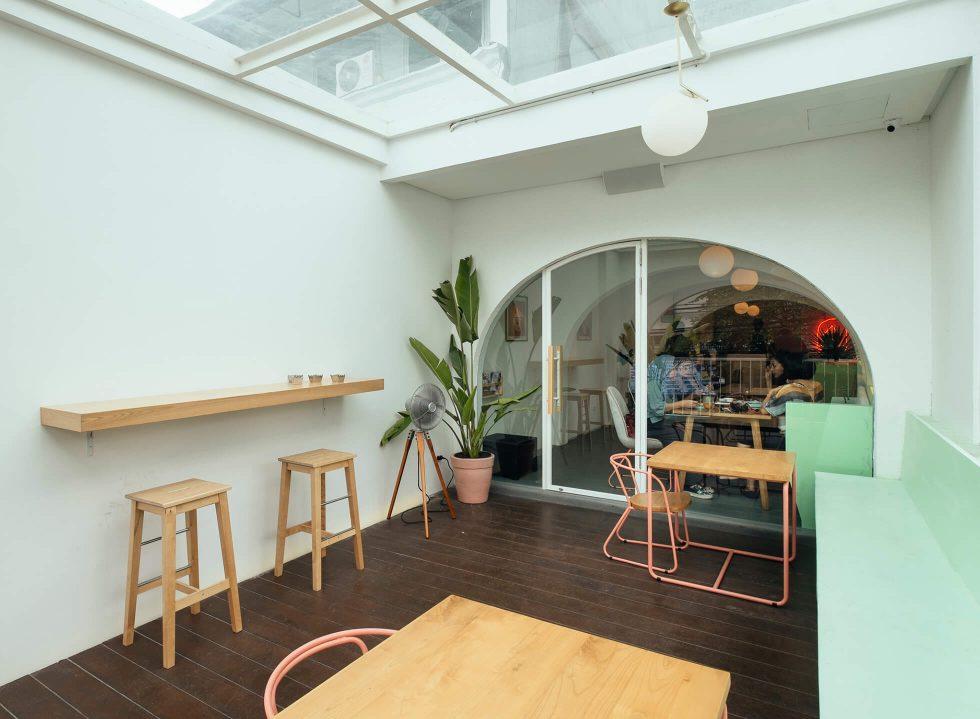 Area semi outdoor dengan atap kaca, coffee shop karya Interra //arsitag.com