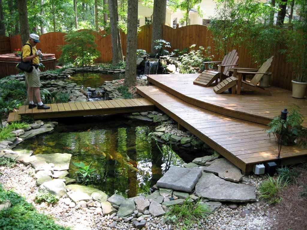 Ruang bersantai outdoor dengan dek kayu di atas kolam ikan // fallhomedecor.org