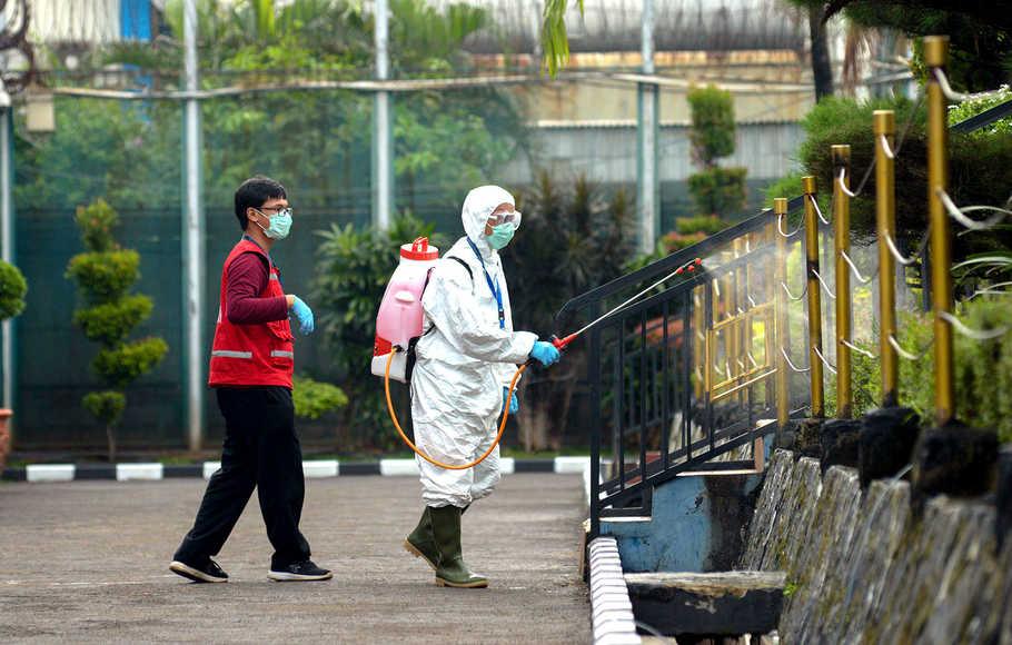 Petugas menyemprotkan cairan disinfektan, via beritasatu.com