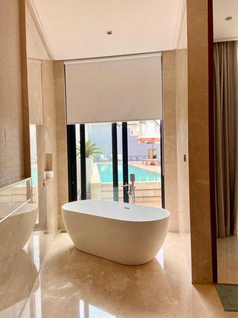 Kamar mandi dengan bathtub dengan jendela langusng menghadap kolam renang // Arsitag.com