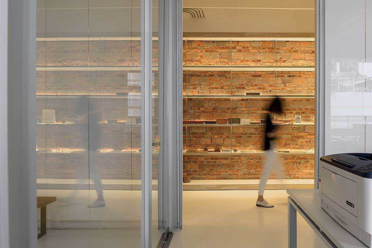 Dinding bata ekspos di salah satu sisi koridor kantor // decoist.com