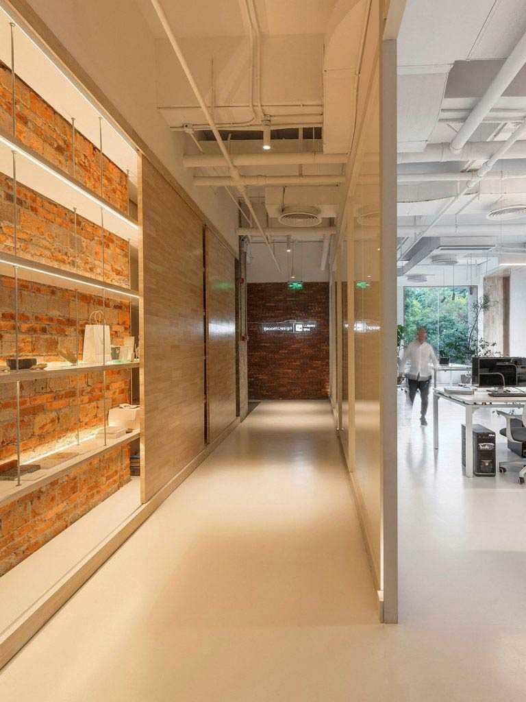 Lorong kantor yang mengkontraskan dinding bata ekspos dan ruang serba putih // decoist.com