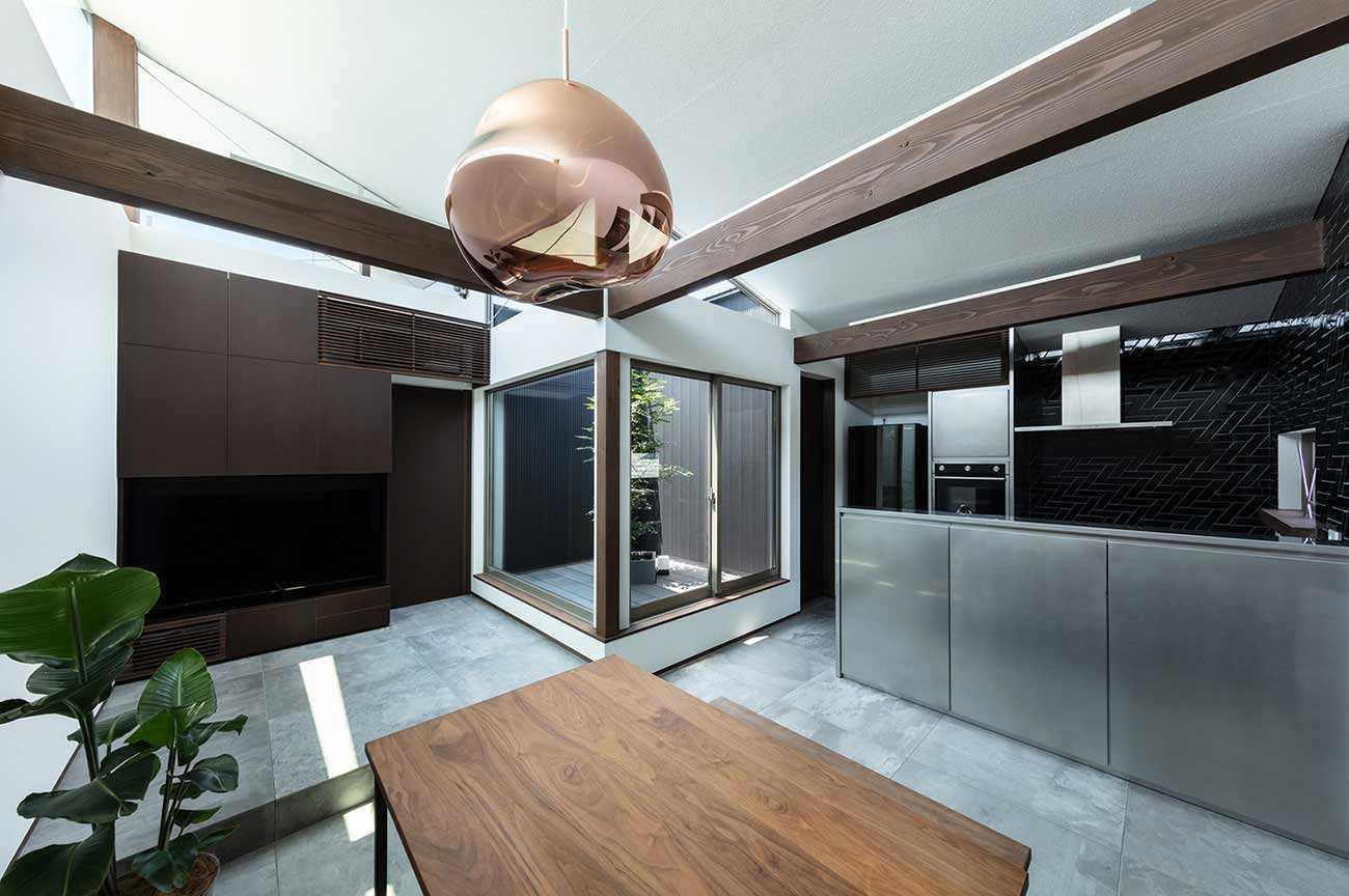 Ruang makan dan dapur dengan pemandangan dry garden // Archdaily.com