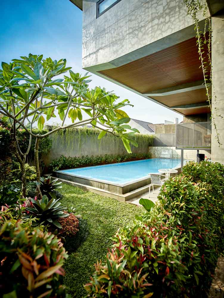 Taman tropis yang rimbun di sisi kolam renang // Archdaily.com