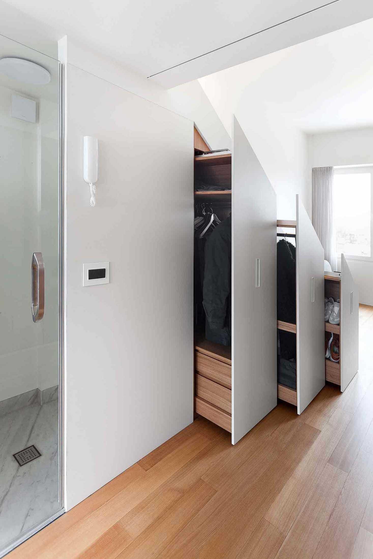 Pemanfaatan ruang di bawah tangga sebagai lemari pakaian karya studio Bazi, via organized-home.com