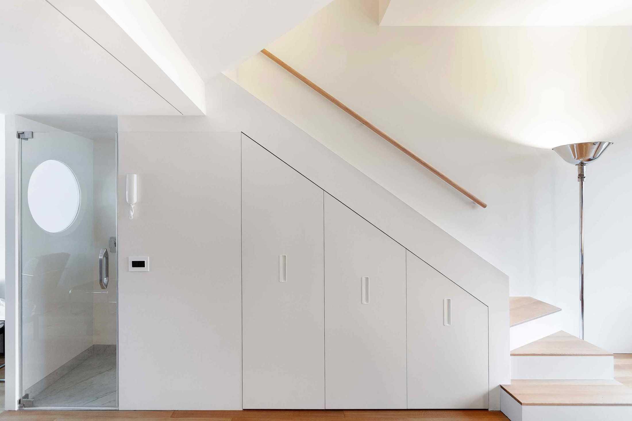 Penempatan kamar mandi mungil di bawah tangga karya studio Bazi, via organized-home.com