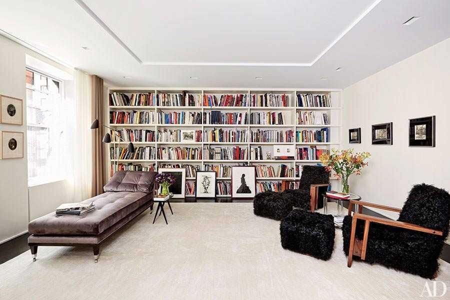 Desain rak buku perpustakaan pribadi dengan sofa nyaman, oleh Thomas Loof, via Architecturaldigest.com