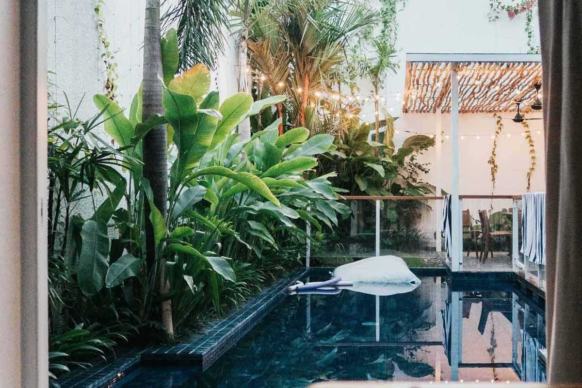 Kolam renang dengan taman gaya tropis, foto oleh Shawn Ang, via unsplash.com
